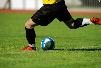 Photo of soccer player kicking a ball. Sports Field Solutions evaluates fields like these for safety and playability.